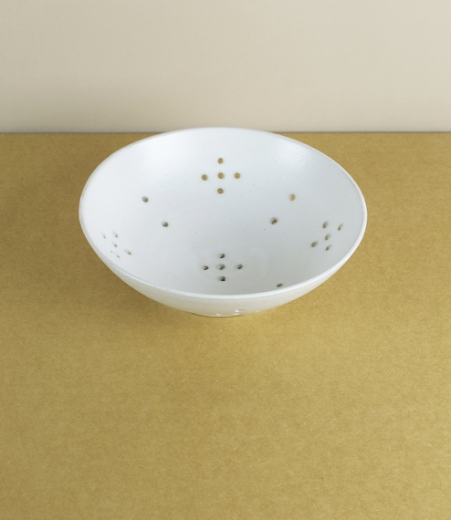 Fat white glazed stoneware berry bowls used for the washing, storage, and serving of berries, soft, and summer fruits, the holes allowing drainage as ..