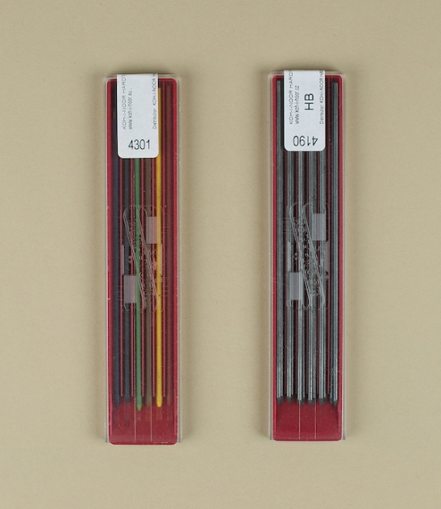 A set of six mechanical coloured pencils with matching 2mm leads, and a natural rubber eraser in a tin box. The pencils are fitted with a small 'V' sh..