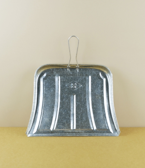 A small simple and lightweight dustpan of galvanised steel fitted with a looped wire handle, all held together without use of welding, rivets, or fast..