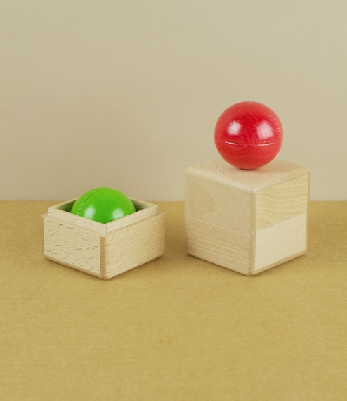An individual green musical ball within a beech-wood box. Simple and beautiful rattles, each colour produces a specific and distinct sound when shaken..