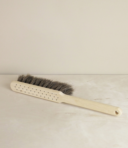 A simple hand stitched hand broom of beech, medium soft grey-brown horse hair, and steel wire. For use with a dustpan as a floor or bench broom. From ..