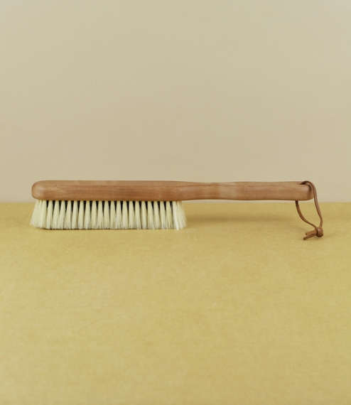 A longer handled medium hard black and white hog hair clothes brush with seven fine dense rows of bristle set into a waxed pear-wood stock. For the du..