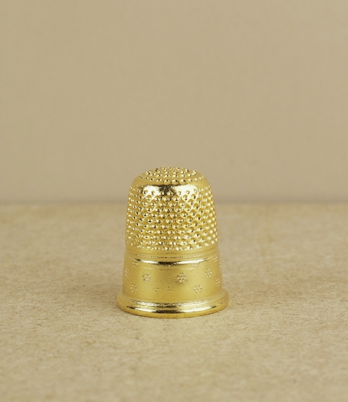 A traditional dressmaker's thimble of gold plated brass. Cast, chased, and plated in France and of a type intended for hard and continuous use by the ..