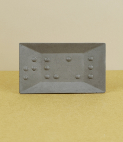 A hand-cast fine 'soft' concrete soap dish embossed with the (Swedish) braille symbols [⠎⠧⠡⠇] which is tvål, the Swedish f..