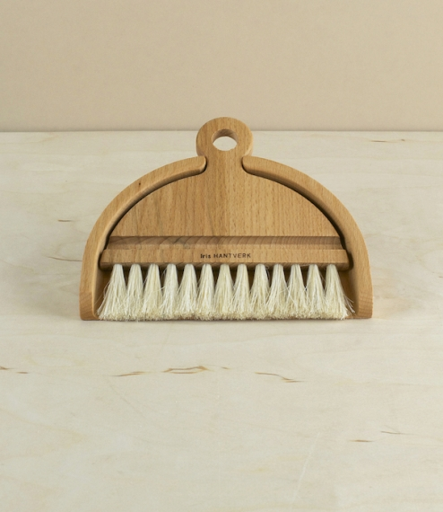 A small oiled beech and horsehair dustpan and brush set designed for sweeping crumbs from the table. The brush fits neatly inside the pan, in a manner..