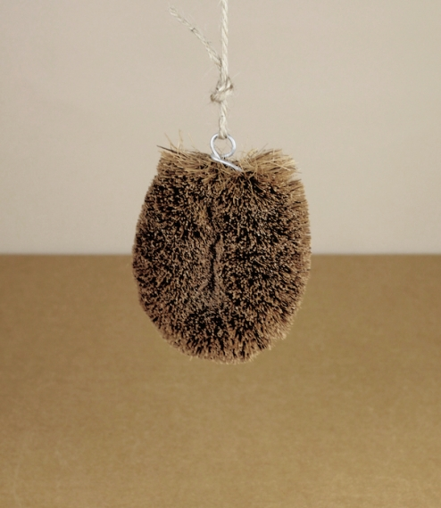 A Japanese 'tawashi' vegetable brush, made from coconut fiber twisted into thick wire and bound with coconut twine. With a hanging loop for st..