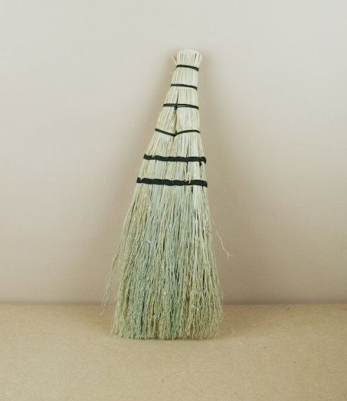 A small sized black twine bound broom of broom-corn or rice-straw, which is neither from rice nor corn, but a kind of sorghum grass traditionally plan..