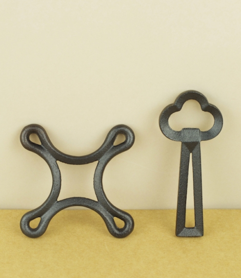 A choice of cast iron bottle openers with a baked black urushi finish, one designed after the shape of a three leafed clover or key, the other being f..