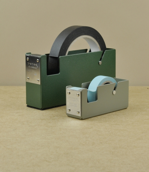 Desk-top or wall mounted tape dispensers with bodies made of a single piece of folded and enamelled sheet steel, with hardened cutting blades, and one..