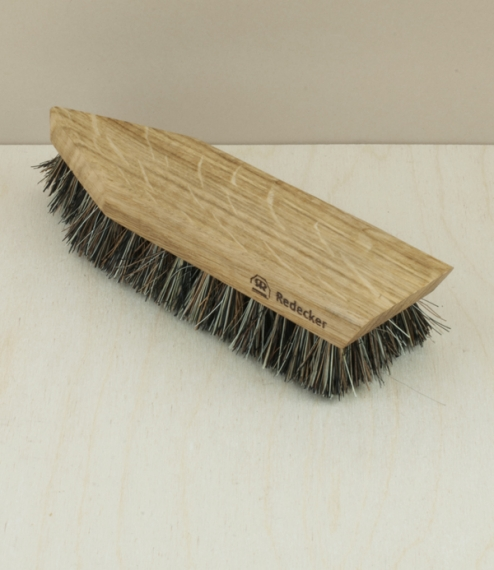 An oiled oak brush with stiff coconut and tampico fibres, for the cleaning of dirt off shoes prior to polishing. The wooden point at the front is for ..