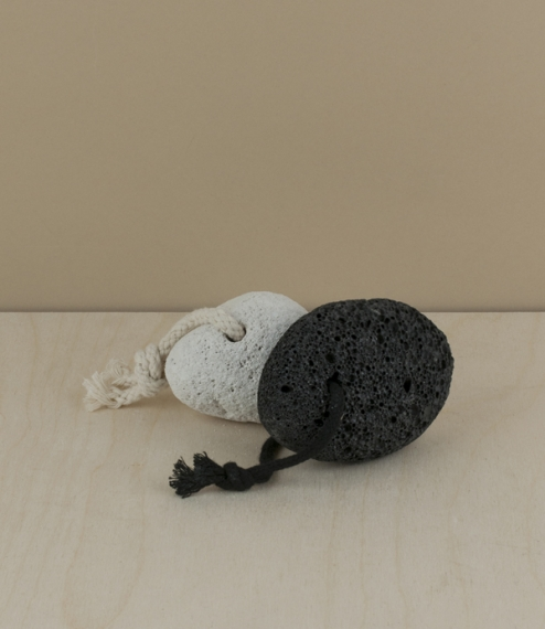 Natural white(ish) or black volcanic pumice stones drilled through and threaded with cotton cord. Used wet to remove calluses and hardened dry skin. P..