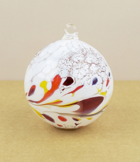 White on clear glass baubles hot dipped into grains of red, yellow, gold, and a little violet or blue, then turned, twisted, and blown to create uniqu...