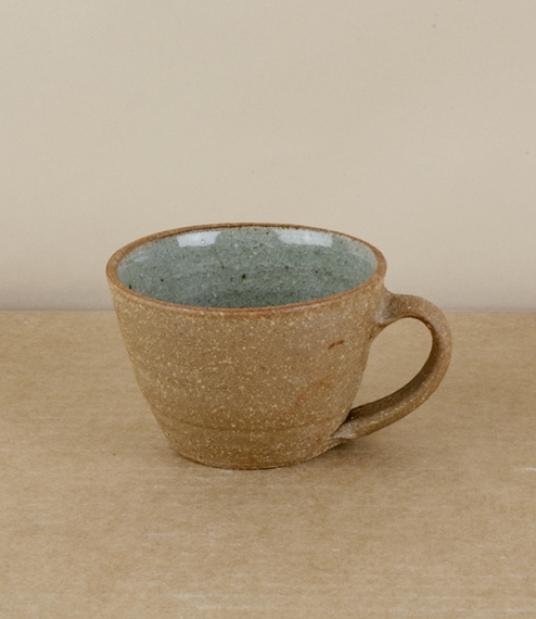 A small flared coffee cup with an internal 'blue grey' glaze. After training in Cardiff and Gothenburg, Sweden, Welbourne set up studio in Cardiff, wh..