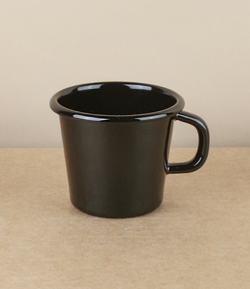 A simple black vitreous enamel on pressed steel coffee cup with a flared straight sided conic sectional form. Holds about 125ml. From the workshops of..