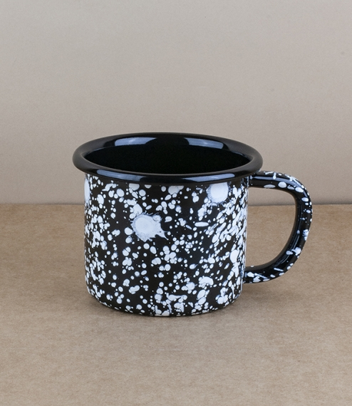 An approximately 9cm diameter, 300ml capacity pressed steel vitreous enamelled mug with white splatter over a black enamel base. Bornn Enamel is a col..