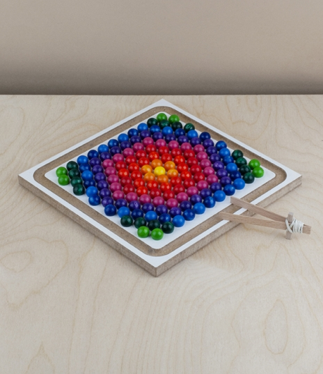 An endlessly creative toy consisting of 250 brightly coloured lacquered wooden balls, and a double sided board, machined on one side with in a square ...