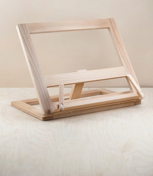 A folding beech wood book stand ideal for use with cookbooks, music books, or for place holding academic texts for reference whilst writing - in fact ..
