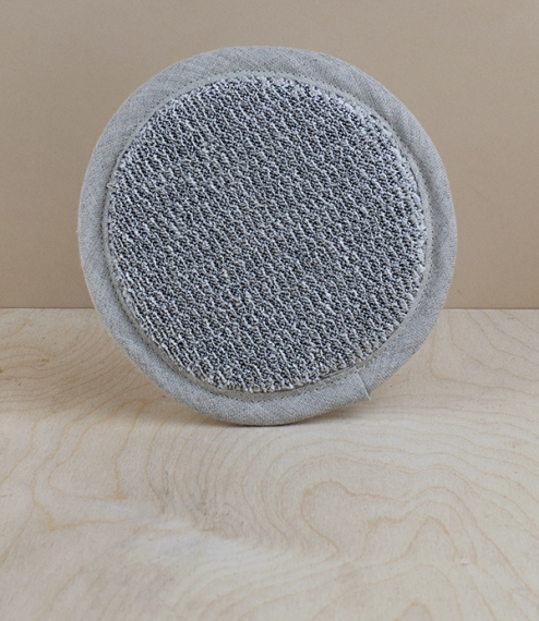 A 100% linen circular cosmetic sponge, with hand strap on the reverse, made from loop- and flat-woven linen, woven by the master weavers at Lapuan Kan..