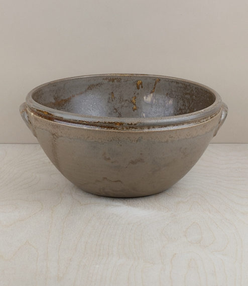 A mottled and variably coloured 'honey' glazed terracotta mixing or serving bowl. Hand shaped, glazed, and finished by the artisans of Maria Terracota..