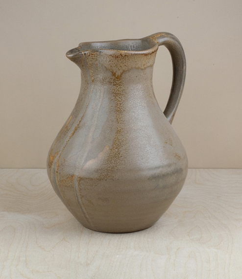A mottled and variably coloured 'honey' glazed terracotta water jug with a capacity of approximately 2.5l. Hand shaped, glazed, and finished by the ar..