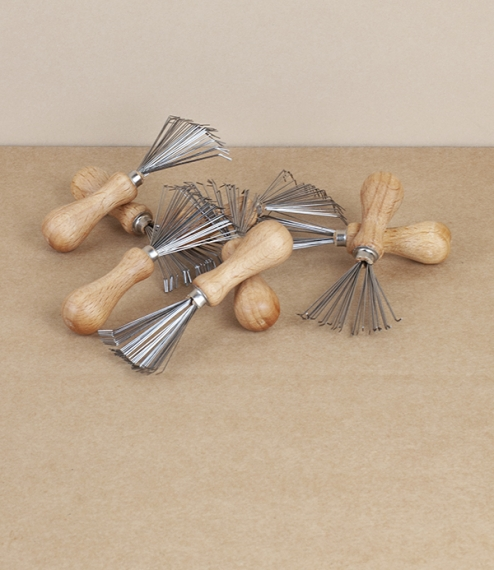 A dainty beech and sprung steel wire rake used to help clear and unclog brushes and combs from unpleasant accumulations of loose hair, dust, fluff, an..