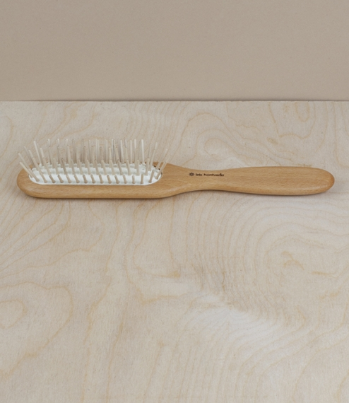 An oiled beech-handled hairbrush set with a flexible natural rubber pad mounted with five rows of smooth tipped wooden pins. A narrow brush head, maki..