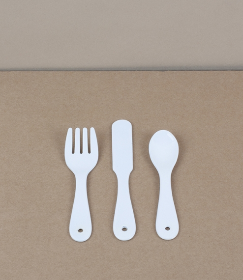 A three piece baby's cutlery set of white vitreous enamel over stainless steel. Enamel is made by the high temperature fusion of powdered glass slurry..