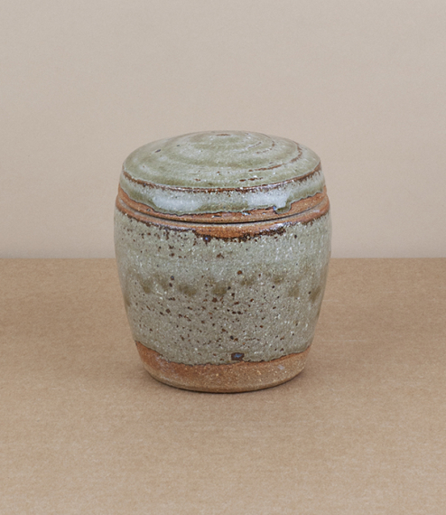 A hand-thrown preserve, condiment, or trinket, jar with a blue-grey nuka glaze. After training in Cardiff and Gothenburg, Sweden, Welbourne set up stu..
