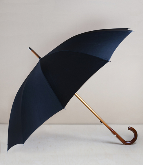 A plain black canopied ten steel rib solid stick umbrella from the workshops of Pierre Vaux in Saint-Claude, in the Jura region of eastern France. Als..