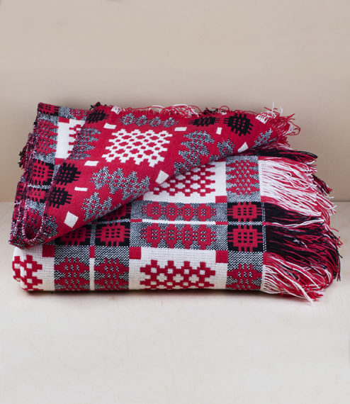 A red, black, and white wool traditional Caernarfon pattern Welsh tapestry blanket or carthen, woven in Cynwyl Elfed, Carmarthenshire on a dobby loom ..
