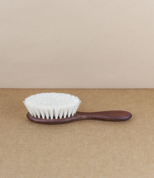 A very soft natural hairbrush of oiled pear-wood, with short fine bristles of white goat hair. For smoothing downy hair and gently massaging the scalp..