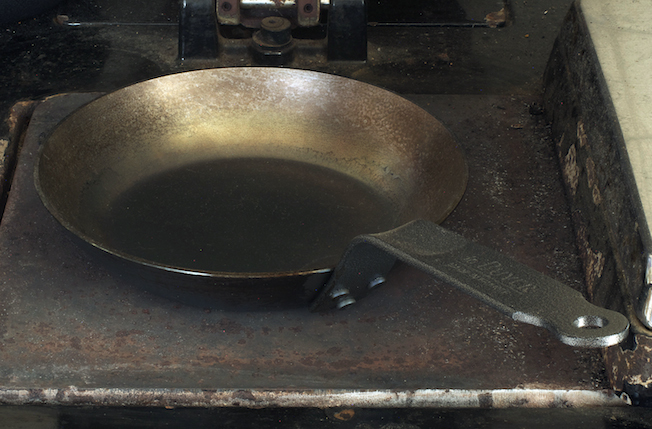 A newly seasoned pan patientely blackening on a hot plate.