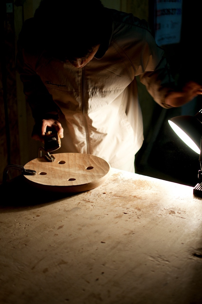Iba Takahito at work on a stool seat by the oblique light of a single lamp.