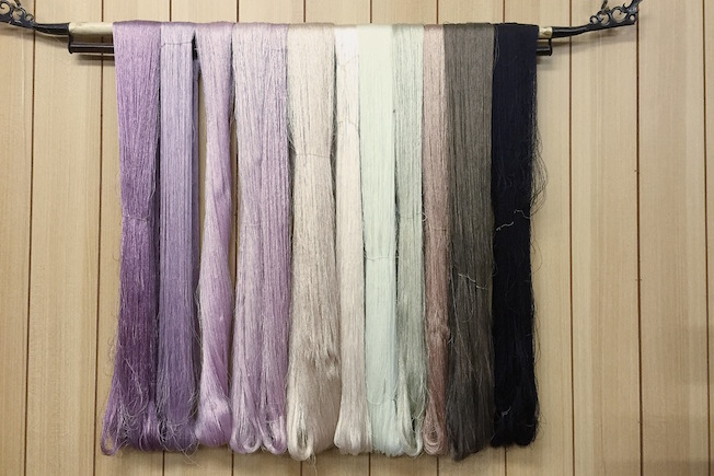 Hanks of naturally dyed silk demonstrating the range of colours.