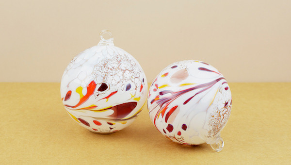 White on clear glass baubles hot dipped into grains of red, yellow, gold, and a little violet or blue, then turned, twisted, and blown to create uniqu..